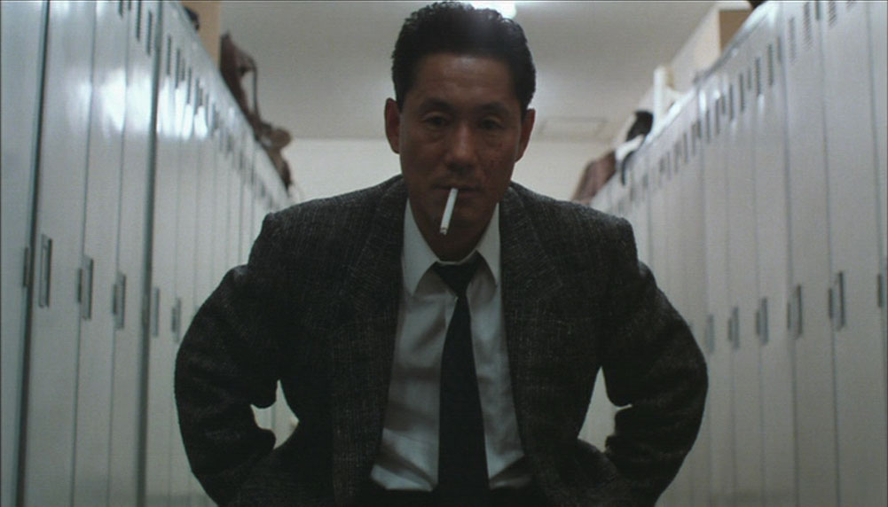 Takeshi Kitano smoking a cigarette (or weed)